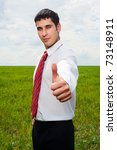 young happy businessman showing thumbs up over green meadow - stock photo