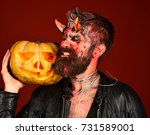 Small photo of Devil or monster with October decorations. Demon with horns and demonic face holds carved jack o lantern. Halloween party concept. Man wearing scary makeup holds pumpkin on bloody red background