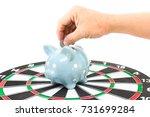 hand putting coin into a piggy... | Shutterstock . vector #731699284