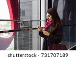 Small photo of Young beautiful lady looking at her mobile phone and staying inside some business center. Modern citizen spends her break hours communicating with clients. Attractive woman stays along in a building.