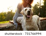 Stock photo cropped shot of young african lady wearing white costume walking with pretty dog in park 731766994