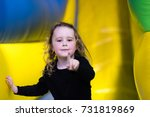 Small photo of Caucasian child on bouncy castle pointing at you happy smiling portrait bright background joyful expression gesturing finger confident girl expressing leadership