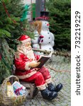 Small photo of Statue of a Santa Clause sitting on a box reading a book with a snowman in the background and evergreen trees all around
