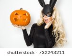 Stock photo beautiful young woman in halloween bunny costume standing beside easter basket and holding pumpkin 732243211