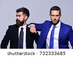 Small photo of Executives present partnership, friendship and strength. Business, confidence and teamwork concept. Businessmen with confident faces in formal suits on grey background. Leaders rely on each other