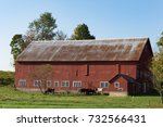 A Rustic Red Barn With Metal...