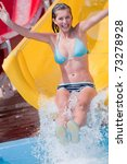 Happy summer vacation - young girl sliding to the water - stock photo