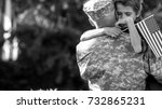 Happy reunion of soldier with family, son hug father. Black and white emotional portrait of american soldier father and his son - stock photo