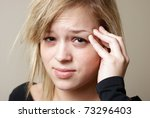 A young woman relieves the pain from her headache by putting pressure on her temple. - stock photo