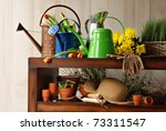 Sunlit still life with assorted gardening supplies, watering cans and fresh cut flowers. - stock photo