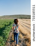 Small photo of Young and carefree woman doing sightseeing in the countryside, in a division area of different crops. Lifestyle portrait.