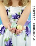 Little girl in her Easter dress holds out two beautifully decorated Easter eggs. - stock photo