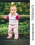 Small photo of Outdoor portrait of adorable baby girl of 9-12 months old playing in the park, wearing white bodywarmer