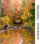 Small photo of Town of Wells, New York - October 8, 2017: A Jeep Wrangler Rubicon charging through a water and mud hole in the Adirondack wilderness in autumn, with a photographer kneeling alongside the trail.