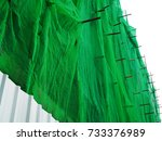Small photo of Green crease plastic construction dust protection mesh cloth, covering building site, with scaffolding iron bars exposed, and steel wavy wall, with bright white sky perspective background