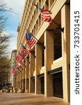 Small photo of Washington, DC, USA April 7, 2009 American flags fly outside of the J Edgar Hoover Building in Washington, DC. The building is the headquarters of the FBI