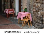 Small photo of Two Italian style made tables in a little ally with wooden chair and flowers on the table, it looks like a spaghetti restaurant, a traditional eatery or italian restaurant