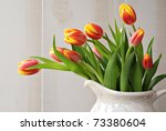 Freshly misted spring tulips in old-fashioned pitcher with cream colored paneling in background.  Closeup with shallow dof. - stock photo