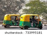 Small photo of Delhi, India - December 2011: Green and yellow coloured auto rickshaws travel along a busy city road.
