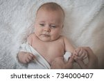 mom dresses the baby on the bed ... | Shutterstock . vector #734000407