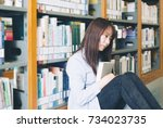 Small photo of Beautiful asian girls reading in the library