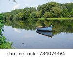 Small photo of Mirror reflection of a old typical wood boat in the Vienne in the Loire Valley on a hot summer day