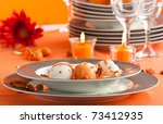 Easter table setting in orange tones with candles and flower. - stock photo