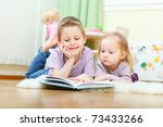 Brother and his little sister at home reading - stock photo