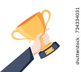 winning cup in hand. symbol of... | Shutterstock . vector #734334031