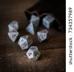 Small photo of Gaming dice on a wooden table top being rolled out of a bag shot in natural light with subdued wood grain colors as background.