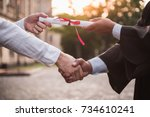 Small photo of Cropped image of graduate in academic dress taking his diplomas and shaking hand