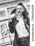 Small photo of Stylish autumn in Paris. happy young fashion-monger in trench coat near Arc de Triomphe in Paris, France showing victory gesture