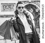 Small photo of Stylish autumn in Paris. elegant fashion-monger in trench coat near Arc de Triomphe in Paris, France with shopping bags looking into the distance