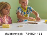girl is rolling out dough to... | Shutterstock . vector #734824411