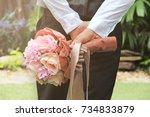the groom holds the flower... | Shutterstock . vector #734833879