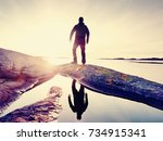 silhouette man on a cliff above ... | Shutterstock . vector #734915341