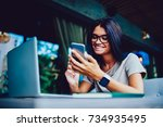 Small photo of Cheerful female student happy getting SMS from boyfriend with doing homework in cafe interior, successful young entrepreneur excite with first business offer sending feedback to colleague on phone