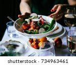 hands passing over a bowl of... | Shutterstock . vector #734963461