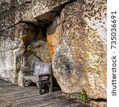 wooden bench in a rock niche | Shutterstock . vector #735036691