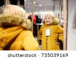 cute little boy trying new coat ... | Shutterstock . vector #735039169