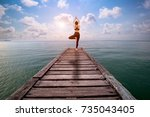 woman practicing yoga at... | Shutterstock . vector #735043405