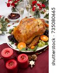 Small photo of Roasted herb rubbed turkey garnished with fresh grapes, oranges, and cranberry is ready for Christmas dinner. Ornaments, Champagne, candles, and other Christmas decorations on feast table.