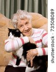 Stock photo the grandmother with a cat on a sofa 73508089