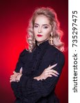 Small photo of Beautiful, young, blond woman in black retro blouse with cross earrings. Mourning attire of a black widow, fashionable portrait on a background of a background. A stern look.