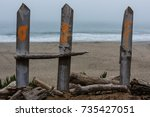 Small photo of A picket fence at the beach spells the abbreviation for Hawaii.