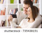happy couple watching on line... | Shutterstock . vector #735438151