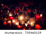 Small photo of candles burning in lanterns at night during All Saints Day