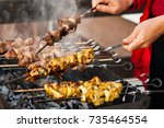 two hands turning skewers with... | Shutterstock . vector #735464554