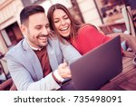 happy couple sitting in street... | Shutterstock . vector #735498091