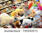 a baby seats at soft toys in a... | Shutterstock . vector #735543571